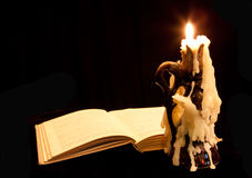 Old book and candle. On dark background Stock Images