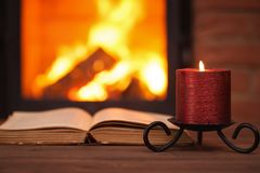Old book and candle in front of fireplace. With vivid flames Stock Photography