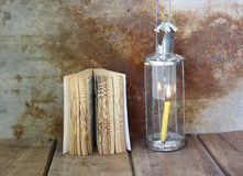Old book and candle lanterns on wooden background. S royalty free stock images