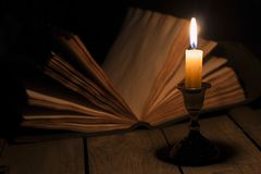 Old book and candle. Old antique magic book opened with burning candle near on the wooden table Stock Photography