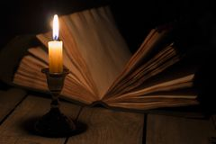 Old book and candle. Old antique magic book opened with burning candle near on the wooden table Stock Photo