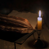 Old book and candle royalty free stock photography
