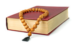 Old book with a claret  cover and wooden rosary. Royalty Free Stock Images