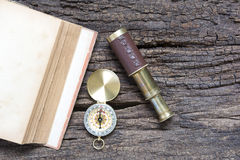 Old book and compass and spyglass on wood panel Royalty Free Stock Photography