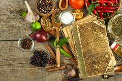 Old book of cookery recipes. Culinary background and recipe book with various spices on wooden table. Old book of cookery recipes. Culinary background and stock image