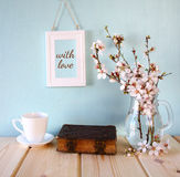 Old book, cup of coffee next to spring white flowers Stock Photography