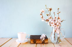 Old book, cup of coffee next to spring white flowers Royalty Free Stock Photos