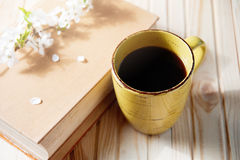 Old book, cup of coffee next to spring white flowers on wooden texture Royalty Free Stock Photos