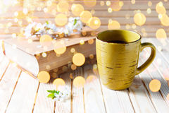 Old book, cup of coffee next to spring white flowers on wooden texture with dold bokeh. Old book, cup of coffee next to spring white flowers on wooden texture Royalty Free Stock Photos