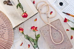 Old book and dry rose and accessories for writing. Retro concept with book and beads Stock Photos
