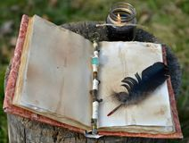 Old book with empty pages, magic wand, quill and black candle. Occult, esoteric, divination and wicca concept. Mystic and vintage background with old objects stock image