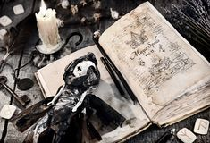 Old book with evil spells, scary doll, rune and burning candle on planks. Halloween, occult, esoteric and wicca concept. Vintage background with old magic royalty free stock photo