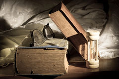 Old book with eye glass and hour glass Stock Photography