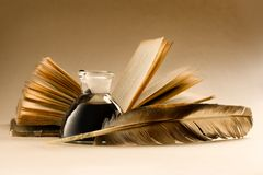 An old book with a feather. And the inkpot full of ink Royalty Free Stock Photos