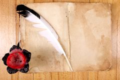 Old Book with feather pen and candle Stock Photo