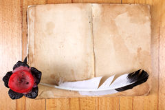 Old Book with feather pen and candle Royalty Free Stock Photography