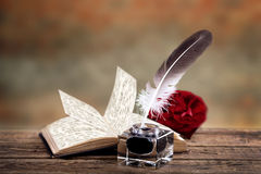 Old book, feather pen and inkwell Stock Photo