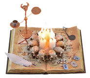 Magic book with candles and runes. Old book with feather, scary candles and metal runes isolated Royalty Free Stock Photos
