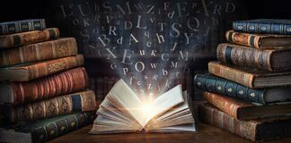 Old book with flying letters and magic light on the background of the bookshelf in the library. Ancient books as a symbol of
