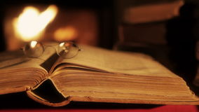 Old book in in front of a fireplace. Old book and glasses in front of the fireplace. Vintage style.Shallow depth of field. Camera traveling right to left stock video footage