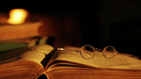 Old book and glasses in front of the fireplace. stock video