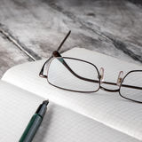 Old book with glasses lay on a table. Royalty Free Stock Images