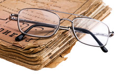 Old book with glasses macro Stock Images