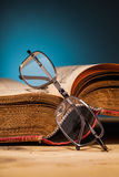 Old book and glasses on wooden table Stock Photo