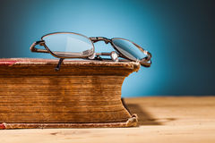 Old book and glasses on wooden table Royalty Free Stock Images