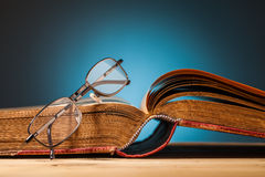 Old book and glasses on wooden table Royalty Free Stock Image