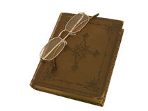 Old book and gold-rimmed spectacles. Old book with a leather cover with cross pattern and gold-rimmed spectacles lying on the book Royalty Free Stock Image