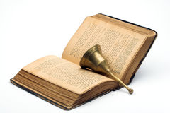 Old book and handbell. Over white Royalty Free Stock Photography