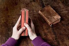 Old book in hands. Very old book in hands - slightly open. with another one, closed, on the desk Stock Photo