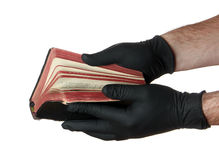 Old book in hands with black gloves Royalty Free Stock Images