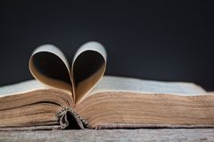 An old book with heart-shaped pages. Dark background royalty free stock images
