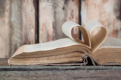 An old book with heart-shaped pages. Wooden background royalty free stock photography