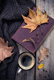 Old book, knitted sweater with autumn leaves and coffee mug Stock Photo
