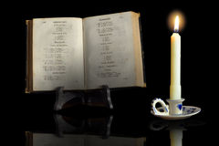 An old book in the light of a candle. An ancient book is illuminated by the light of a candle stock photos