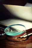 Old book and magnifier Royalty Free Stock Images