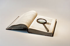 Old book and magnifier Stock Image