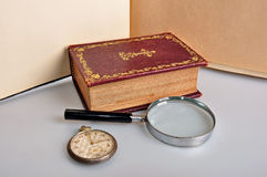 Old book magnifier and watch Royalty Free Stock Photography