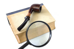 Old book and magnifying glass Stock Photography