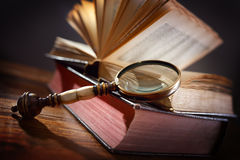 Old book and magnifying glass Royalty Free Stock Photos