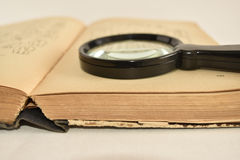 Old book with magnifying glass, white background Stock Photos
