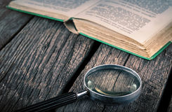 Old book and magnifying glass on wood Royalty Free Stock Images