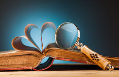Old book  and magnifying glass on wooden table Royalty Free Stock Photography