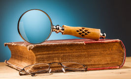 Old book  and magnifying glass on wooden table Stock Photography