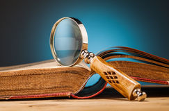 Old book  and magnifying glass on wooden table Royalty Free Stock Image