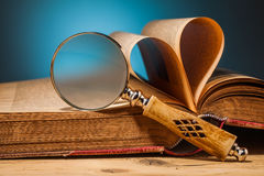 Old book  and magnifying glass on wooden table Royalty Free Stock Photos