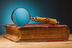 Old book  and magnifying glass on wooden table Royalty Free Stock Images